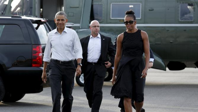 U.S. President Barack Obama and first lady Michelle Obama walk from Marine One upon their arrival in Martha's Vineyard, Massachusetts August 7, 2015.  REUTERS/Kevin Lamarque