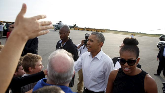 U.S. President Barack Obama and first lady Michelle Obama greet well wishers upon their arrival in Martha's Vineyard, Massachusetts August 7, 2015.  REUTERS/Kevin Lamarque