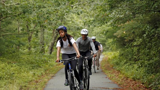 U.S. President Barack Obama trails his daughter Malia as the Obama family takes a bike ride on Martha's Vineyard in Massachusetts August 22, 2015. Obama is on a two-week vacation on the Vineyard. REUTERS/Kevin Lamarque TPX IMAGES OF THE DAY TPX IMAGES OF THE DAY