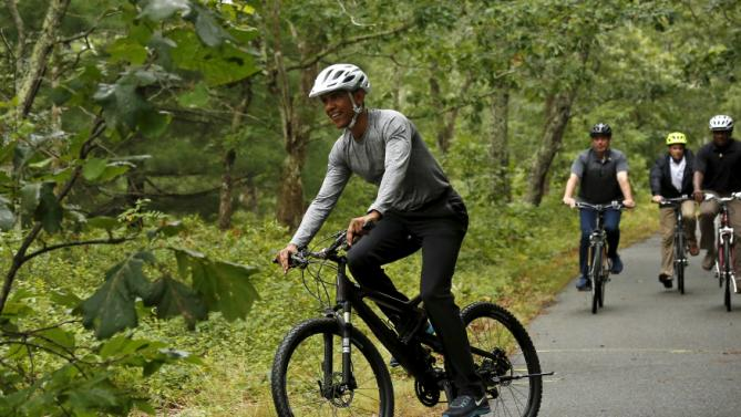 U.S. President Barack Obama takes a bike ride with his family on Martha's Vineyard in Massachusetts August 22, 2015. Obama is on a two-week vacation on the Vineyard. REUTERS/Kevin Lamarque