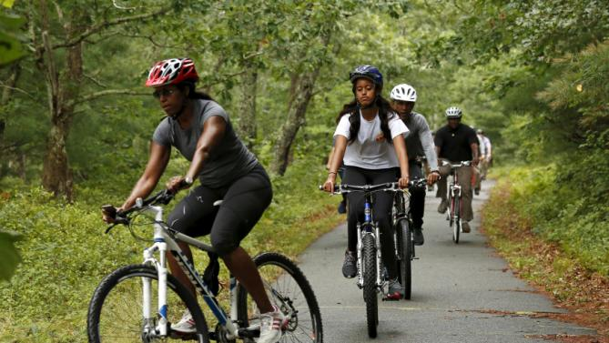 U.S. President Barack Obama trails first lady Michelle Obama (L) and daughter Malia (2nd L) as the Obama family takes a bike ride on Martha's Vineyard in Massachusetts August 22, 2015. Obama is on a two-week vacation on the Vineyard. REUTERS/Kevin Lamarque