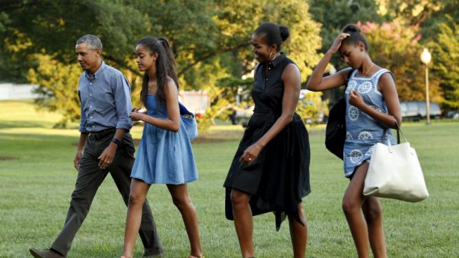 U.S. President Barack Obama (L) walks with First lady Michelle Obama (2nd R) and their daugthers Malia and Sasha on the South Lawn of the White House upon their return to Washington following a two-week vacation on Martha's Vineyard in Massachusetts August 23, 2015. REUTERS/Yuri Gripas