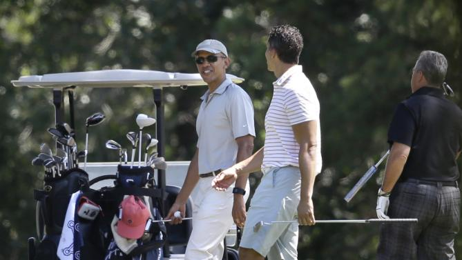 President Barack Obama, left, speaks with Cyrus Walker, right, cousin of White House senior adviser Valerie Jarrett, while golfing Saturday, Aug. 8, 2015, at Farm Neck Golf Club, in Oak Bluffs, Mass., on the island of Martha's Vineyard. Obama is spending his first full day of vacation on the island playing golf. (AP Photo/Steven Senne)