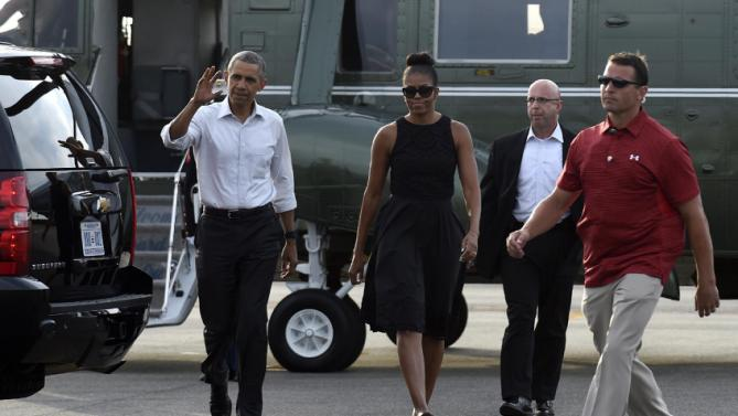 President Barack Obama and first lady Michelle Obama walk over to greet people after arriving at Vineyard Haven on Martha's Vineyard, Mass., Friday, Aug. 7, 2015. The president is returning to his summer vacation spot of choice, the Massachusetts island of Martha's Vineyard, for more than two weeks of hoped-for rest coupled with extended pursuit of his favorite leisure sport: golf. (AP Photo/Susan Walsh)
