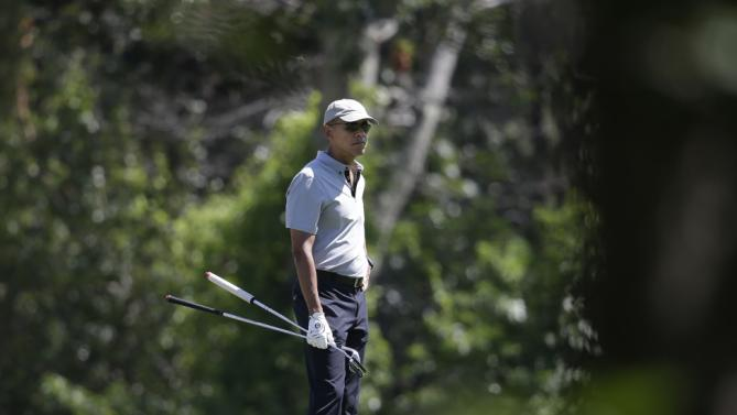 President Barack Obama holds clubs as he stands on a green while golfing, Wednesday, Aug. 12, 2015, at Farm Neck Golf Club, in Oak Bluffs, Mass., on the island of Martha's Vineyard. The president, first lady Michelle Obama, and daughter Sasha are vacationing on the island. (AP Photo/Steven Senne)