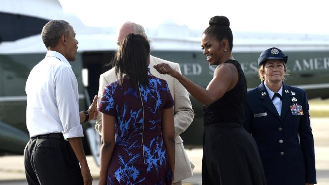 President Barack Obama, left, talks with Rep. Bill Keating, D-Mass, second from left, as first lady Michelle Obama, second from right, looks to Sasha Obama, center, after they arrived at Air Station Cape Cod, in Mass., Friday, Aug. 7, 2015. The president is returning to his summer vacation spot of choice, the Massachusetts island of Martha's Vineyard, for more than two weeks of hoped-for rest coupled with extended pursuit of his favorite leisure sport: golf. 102nd Intelligence Wing Command Chief Master Sgt. Karen Cozza is at right. (AP Photo/Susan Walsh)