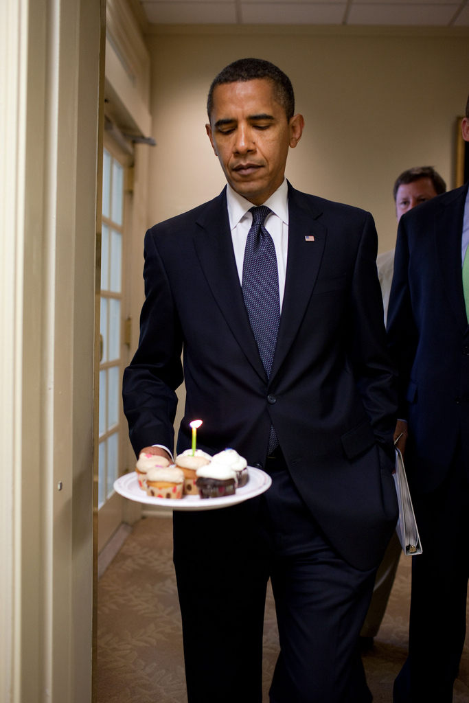 President Barack Obama watches the flame on the candle as he walks to the Brady Briefing Room to present cupcakes to Hearst White House columnist Helen Thomas in honor of her birthday, August 4, 2009. Thomas, who turned 89,  shares the same birthday as Obama, who turned 48 years old. (Official White House Photo by Pete Souza) This official White House photograph is being made available only for publication by news organizations and/or for personal use printing by the subject(s) of the photograph. The photograph may not be manipulated in any way and may not be used in commercial or political materials, advertisements, emails, products, promotions that in any way suggests approval or endorsement of the President, the First Family, or the White House.