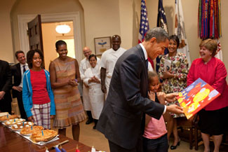 President Barack Obama, with daughter Sasha, looks at the card given  to him during a birthday party with his staff in the Roosevelt Room of the White House,  August 4, 2009.  Daughter Malia nd First Lady Michelle Obama look on at left.  (Official White House Photo by Pete Souza) This official White House photograph is being made available only for publication by news organizations and/or for personal use printing by the subject(s) of the photograph. The photograph may not be manipulated in any way and may not be used in commercial or political materials, advertisements, emails, products, promotions that in any way suggests approval or endorsement of the President, the First Family, or the White House.
