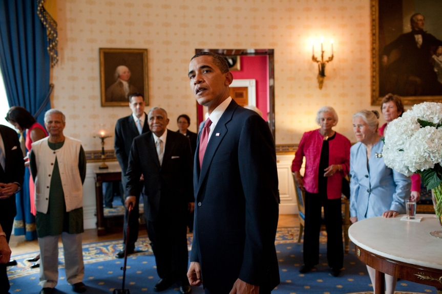President Barack Obama waits in the Blue Room of the White House for the start of an East Room ceremony to present 16 individuals the Presidential Medal of Freedom, August 12, 2009. Standing in the background, from left, are Presidential Medal of Freedom recipients; Muhammad Yunus, Stuart Milk, nephew of slain San Francisco councilman Harvey Milk, Rev. Joseph Lowery, Supreme Court Justice Sandra Day O'Connor, Dr. Janet Davison Rowley, and former President of Ireland Mary Robinson. (Official White House photo by Pete Souza) This official White House photograph is being made available only for publication by news organizations and/or for personal use printing by the subject(s) of the photograph. The photograph may not be manipulated in any way and may not be used in commercial or political materials, advertisements, emails, products, promotions that in any way suggests approval or endorsement of the President, the First Family, or the White House.