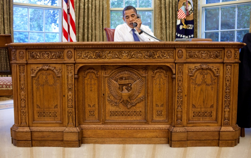 President Barack Obama sits behind the Resolute Desk in the Oval Office during a conference call with people of faith, August 19, 2009. Official White House Photograph by Pete Souza. This official White House photograph is being made available only for publication by news organizations and/or for personal use printing by the subject(s) of the photograph. The photograph may not be manipulated in any way and may not be used in commercial or political materials, advertisements, emails, products, promotions that in any way suggests approval or endorsement of the President, the First Family, or the White House.