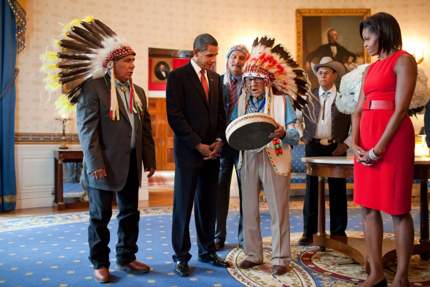 Presidential Medal of Freedom recipient Joseph Medicine Crow shows a drum to President Barack Obama and First Lady Michelle Obama during a reception for recipients and their families in the Blue Room of the White House, August 12, 2009. (Official White House photo by Pete Souza) This official White House photograph is being made available only for publication by news organizations and/or for personal use printing by the subject(s) of the photograph. The photograph may not be manipulated in any way and may not be used in commercial or political materials, advertisements, emails, products, promotions that in any way suggests approval or endorsement of the President, the First Family, or the White House.