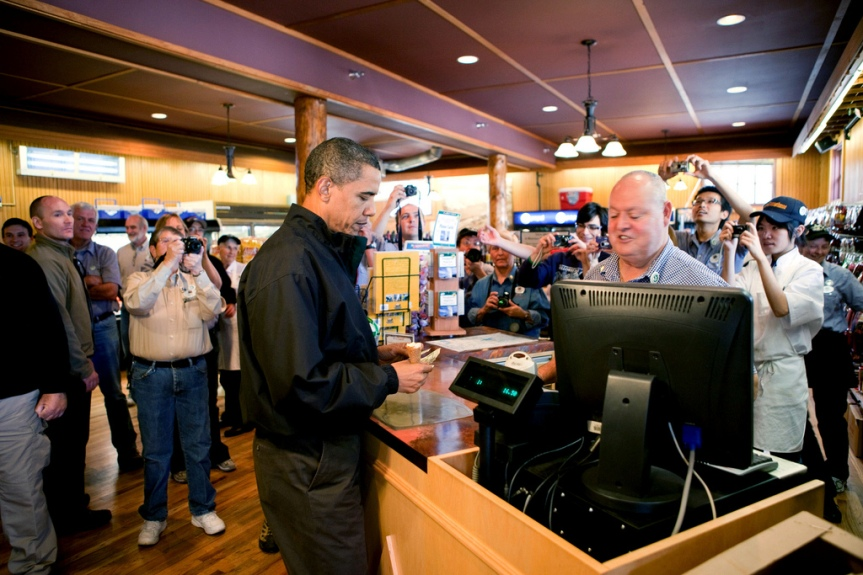 President Barack Obama pays for the family's ice cream during a stop at a store while visiting Yellowstone National Park, August 15, 2009. (Official White House photo by Pete Souza) This official White House photograph is being made available only for publication by news organizations and/or for personal use printing by the subject(s) of the photograph. The photograph may not be manipulated in any way and may not be used in commercial or political materials, advertisements, emails, products, promotions that in any way suggests approval or endorsement of the President, the First Family, or the White House.