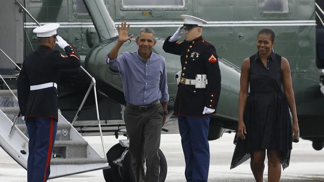 President Barack Obama and first lady Michelle Obama walk to greet supporters as they exit Marine One at the Cape Cod Coast Guard Station in Bourne, Mass., Sunday, Aug. 23, 2015, en route to Washington. (AP Photo/Stew Milne)