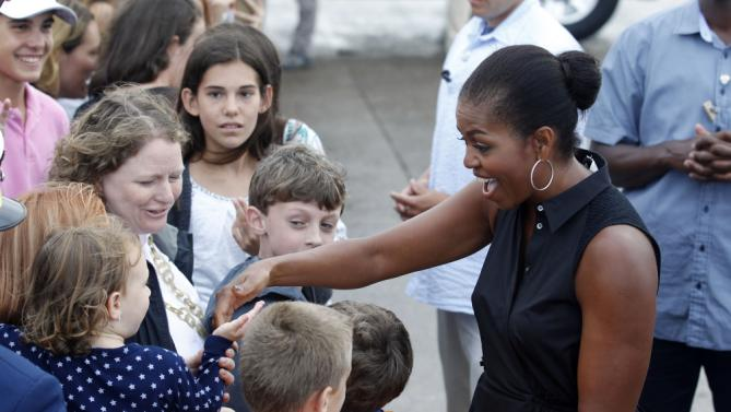 First lady Michelle Obama greets supporters on the tarmac of the Cape Cod Coast Guard Station in Bourne, Mass., Sunday, Aug. 23, 2015, before boarding Air Force One en route to Washington. (AP Photo/Stew Milne)