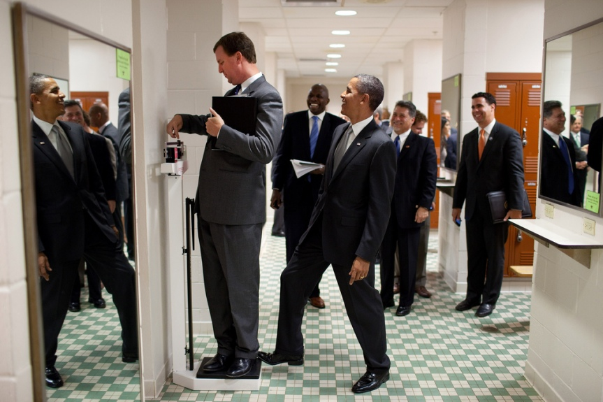 President Barack Obama puts his toe on the scale as Trip Director Marvin Nicholson tries to weigh himself during a hold in the volleyball locker room at the University of Texas in Austin, Texas, Aug. 9, 2010.  (Official White House Photo by Pete Souza) This official White House photograph is being made available only for publication by news organizations and/or for personal use printing by the subject(s) of the photograph. The photograph may not be manipulated in any way and may not be used in commercial or political materials, advertisements, emails, products, promotions that in any way suggests approval or endorsement of the President, the First Family, or the White House.