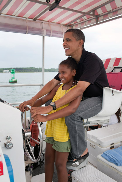 "President Barack Obama and daughter Sasha steer the ""Bay Point Lady"" during a tour of St. Andrews Bay off Panama City Beach, Fla., Aug. 15, 2010 (Official White House Photo by Pete Souza) This official White House photograph is being made available only for publication by news organizations and/or for personal use printing by the subject(s) of the photograph. The photograph may not be manipulated in any way and may not be used in commercial or political materials, advertisements, emails, products, promotions that in any way suggests approval or endorsement of the President, the First Family, or the White House."
