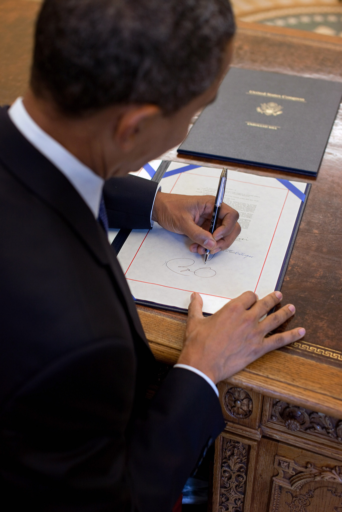 President Barack Obama signs H.R. 2097, the Star-Spangled Banner Commemorative Coin Act, at the Resolute Desk in the Oval Office, Aug. 16, 2010. (Official White House Photo by Pete Souza) This official White House photograph is being made available only for publication by news organizations and/or for personal use printing by the subject(s) of the photograph. The photograph may not be manipulated in any way and may not be used in commercial or political materials, advertisements, emails, products, promotions that in any way suggests approval or endorsement of the President, the First Family, or the White House.