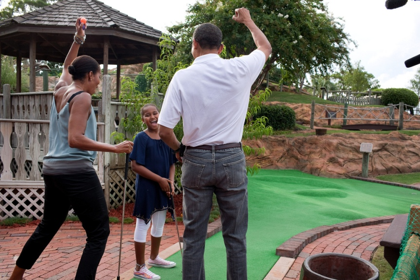 President Barack Obama and First Lady Michelle Obama react to daughter Sasha's hole in one while playing miniature golf at Pirate's Island Golf in Panama City Beach, Fla., Saturday, Aug. 14, 2010. (Official White House Photo by Pete Souza) This official White House photograph is being made available only for publication by news organizations and/or for personal use printing by the subject(s) of the photograph. The photograph may not be manipulated in any way and may not be used in commercial or political materials, advertisements, emails, products, promotions that in any way suggests approval or endorsement of the President, the First Family, or the White House.