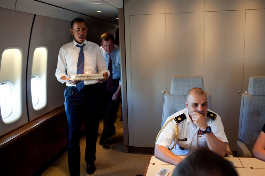 President Barack Obama presents a birthday cake to Military Aide Major Barrett Bernard aboard Air Force One during the flight from Seattle, Wash., to Columbus, Ohio, Aug. 17, 2010. (Official White House Photo by Pete Souza) This official White House photograph is being made available only for publication by news organizations and/or for personal use printing by the subject(s) of the photograph. The photograph may not be manipulated in any way and may not be used in commercial or political materials, advertisements, emails, products, promotions that in any way suggests approval or endorsement of the President, the First Family, or the White House.