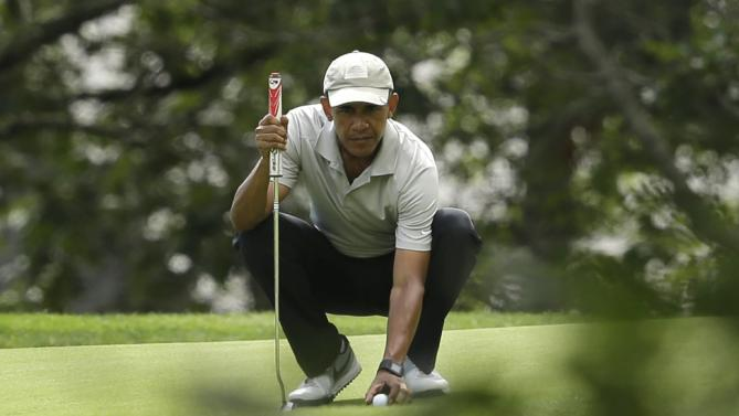 President Barack Obama places his ball on the green before putting while golfing Sunday, Aug. 23, 2015, at Farm Neck Golf Club, in Oak Bluffs, Mass., on the island of Martha's Vineyard. (AP Photo/Steven Senne)