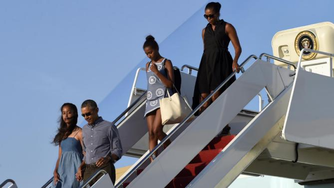 President Barack Obama, second from left, holding hands with his daughter Malia Obama, left, walks off of Air Force One as daughter Sasha Obama, second from right, and first lady Michelle Obama, right, follow at Andrews Air Force Base in Md., Sunday, Aug. 23, 2015. The president is returning to Washington after he and his family spent more than two weeks vacationing on the Massachusetts island of Martha's Vineyard. (AP Photo/Susan Walsh)