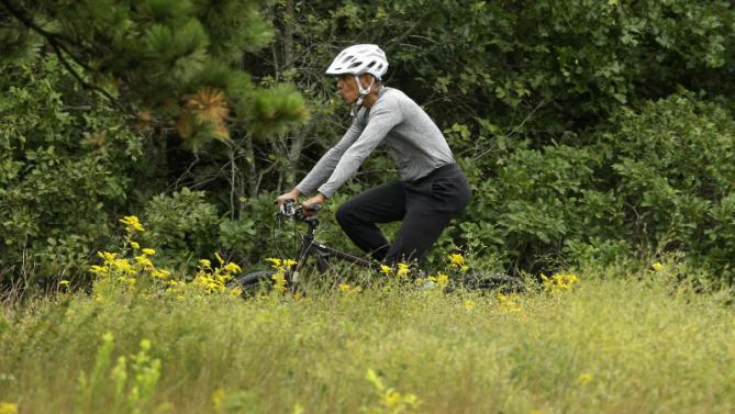 President Barack Obama rides a bike Saturday, Aug. 22, 2015, in West Tisbury, Mass., on the island of Martha's Vineyard. Obama and his family vacation every August on Martha's Vineyard. (AP Photo/Steven Senne)