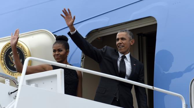 President Barack Obama and first lady Michelle Obama waves from the top of Air Force One at Andrews Air Force Base, Md., Friday, Aug. 7, 2015. The president will return to his summer vacation spot of choice, the Massachusetts island of Martha's Vineyard, for more than two weeks of hoped-for rest coupled with extended pursuit of his favorite leisure sport: golf. (AP Photo/Susan Walsh)