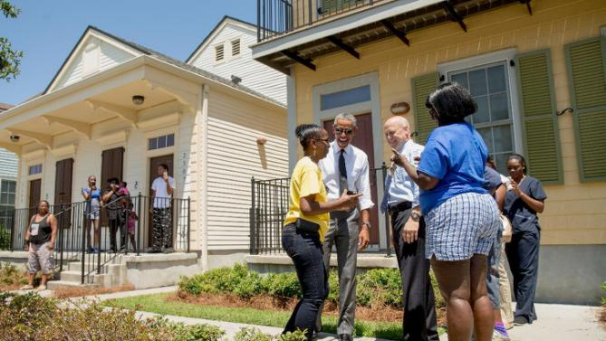 President Barack Obama, accompanied by New Orleans Mayor Mitch Landrieu, third from right, greets residents in the the Tremé neighborhood in New Orleans, Thursday, Aug. 27, 2015, for the 10th anniversary since the devastation of Hurricane Katrina. Tremé is one of the oldest black neighborhoods in America, which borders the French Quarter just north of Downtown. (AP Photo/Andrew Harnik)