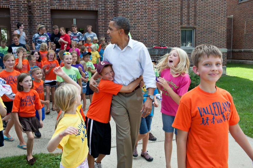 President Barack Obama greets children from the Valleyland Kids summer program outside a school in Chatfield, Minn., during a three-day bus tour in the Midwest, Aug. 15, 2011. (Official White House Photo by Pete Souza) This official White House photograph is being made available only for publication by news organizations and/or for personal use printing by the subject(s) of the photograph. The photograph may not be manipulated in any way and may not be used in commercial or political materials, advertisements, emails, products, promotions that in any way suggests approval or endorsement of the President, the First Family, or the White House.