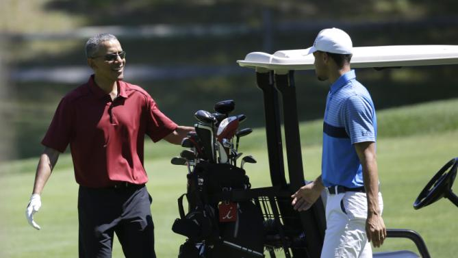 President Barack Obama, left, speaks with NBA basketball player Stephen Curry, right, while golfing Friday, Aug. 14, 2015, at Farm Neck Golf Club, in Oak Bluffs, Mass., on the island of Martha's Vineyard. The president, first lady Michelle Obama, and daughter Sasha are vacationing on the island. (AP Photo/Steven Senne)