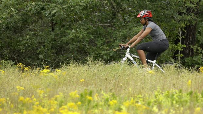 First lady Michelle Obama rides a bike, Saturday, Aug. 22, 2015, in West Tisbury, Mass., on the island of Martha's Vineyard. President Barack Obama and his family vacation every August on the island. (AP Photo/Steven Senne)