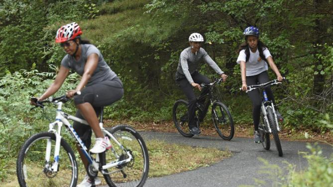 President Barack Obama, his daughter Malia, right, and first lady Michelle Obama, left, ride their bikes in West Tisbury, Mass., on Martha's Vineyard, Saturday, Aug. 22, 2015. Obama and his family vacation every August on Martha's Vineyard. (AP Photo/Susan Walsh)