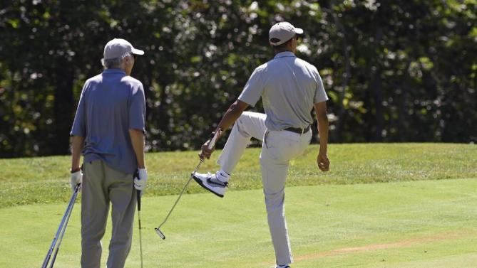 President Barack Obama, right, watches his ball as he plays golf on the first hole with Larry David, left, at Farm Neck Golf Course in Oak Bluffs, Mass., on Martha's Vineyard, Saturday, Aug. 8, 2015. The president is returning to his summer vacation spot of choice, the Massachusetts island of Martha's Vineyard, for more than two weeks of hoped-for rest coupled with extended pursuit of his favorite leisure sport: golf. (AP Photo/Susan Walsh)