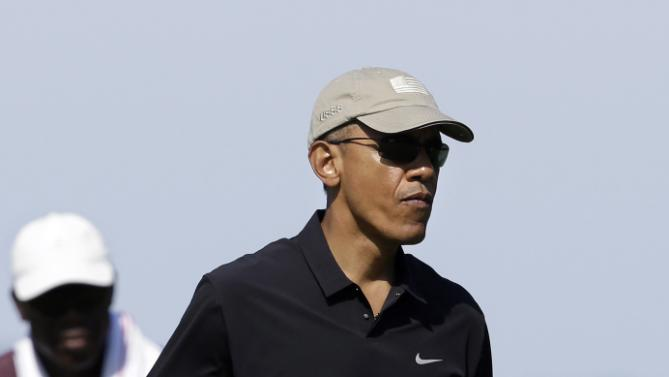 President Barack Obama carries a club as he walks toward a green while golfing Monday, Aug. 10, 2015, at Vineyard Golf Club, in Edgartown, Mass., on the island of Martha's Vineyard. The president is staying on Martha's Vineyard with first lady Michelle Obama and daughter Sasha for a 17-day island retreat. (AP Photo/Steven Senne)
