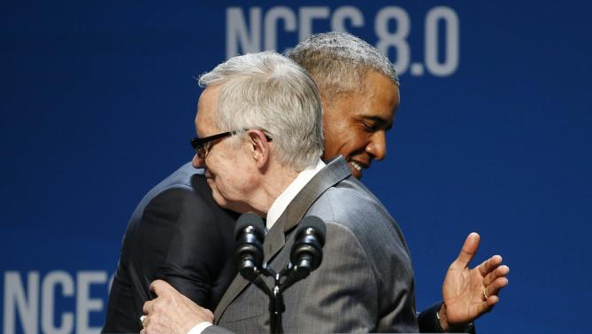 President Barack Obama, right, and Senate Minority Leader Sen. Harry Reid of Nev. embrace on stage at the National Clean Energy Summit Monday, Aug. 24, 2015, in Las Vegas. The President is scheduled to spend the night in Nevada. (AP Photo/John Locher)