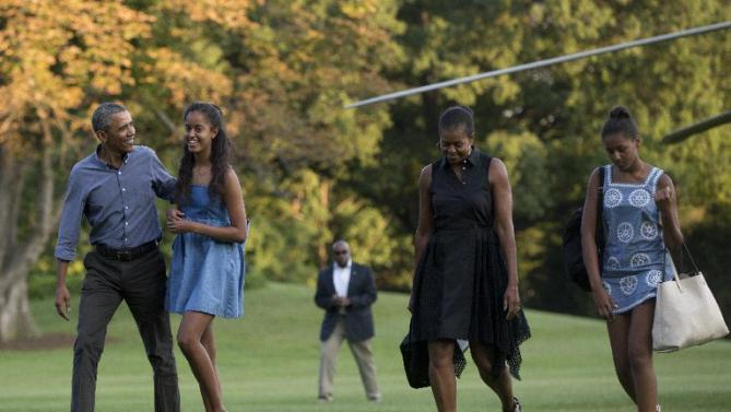 From left, President Barack Obama with daughter Malia and first lady Michelle Obama with daughter Sasha, walk form Marine One across the South Lawn of the White House in Washington, Sunday, Aug. 23, 2015, as they return form a family vacation on Martha's Vineyard. (AP Photo/Carolyn Kaster)