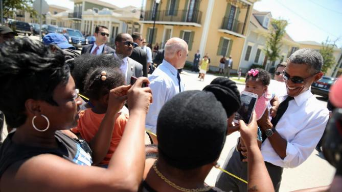 President Barack Obama, accompanied by New Orleans Mayor Mitch Landrieu, holds a child as he greets residents in the the Tremé neighborhood in New Orleans, Thursday, Aug. 27, 2015, for the 10th anniversary since the devastation of Hurricane Katrina. Tremé is one of the oldest black neighborhoods in America, which borders the French Quarter just north of Downtown.(AP Photo/Andrew Harnik)