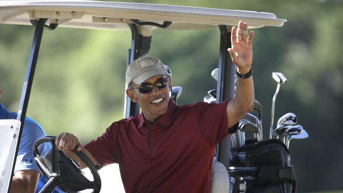 President Barack Obama waves to people from a golf cart while golfing Friday, Aug. 14, 2015, at Farm Neck Golf Club, in Oak Bluffs, Mass., on the island of Martha's Vineyard. The president, first lady Michelle Obama, and daughter Sasha are vacationing on the island. (AP Photo/Steven Senne)