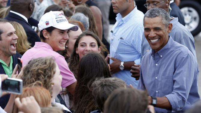 President Barack Obama greets supporters after landing on Marine One at the Cape Cod Coast Guard Station in Bourne, Mass., Sunday, Aug. 23, 2015, en route to Washington. (AP Photo/Stew Milne)
