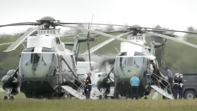 President Barack Obama, third from right, and first lady Michelle Obama, fourth from right, board Marine One, Sunday, Aug. 23, 2015, at an airfield in Edgartown, Mass., on the island of Martha's Vineyard. The President and his family departed the island Sunday following a vacation that was over two weeks in length. (AP Photo/Steven Senne)