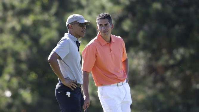 President Barack Obama, left, speaks with Cyrus Walker, right, cousin of White House senior adviser Valerie Jarrett, while golfing Wednesday, Aug. 12, 2015, at Farm Neck Golf Club, in Oak Bluffs, Mass., on the island of Martha's Vineyard. The president, first lady Michelle Obama, and daughter Sasha are vacationing on the island. (AP Photo/Steven Senne)
