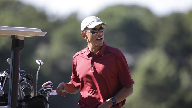 President Barack Obama stands near a cart while golfing Friday, Aug. 14, 2015, at Farm Neck Golf Club, in Oak Bluffs, Mass., on the island of Martha's Vineyard. The president, first lady Michelle Obama, and daughter Sasha are vacationing on the island. (AP Photo/Steven Senne)