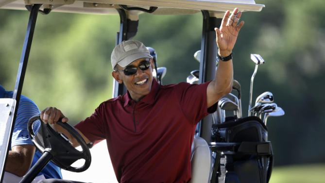 President Barack Obama waves from a golf cart while golfing, Friday, Aug. 14, 2015, at Farm Neck Golf Club, in Oak Bluffs, Mass., on the island of Martha's Vineyard. The president, first lady Michelle Obama, and daughter Sasha are vacationing on the island. (AP Photo/Steven Senne)