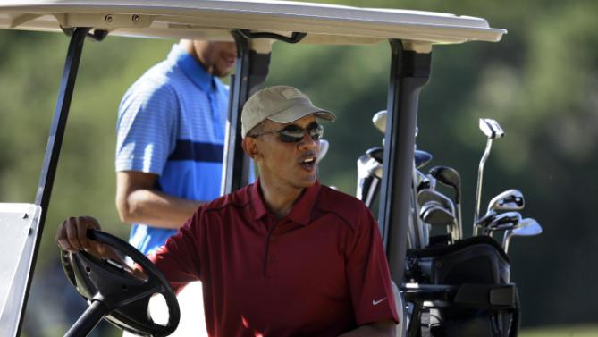 President Barack Obama speaks to people from a golf cart while golfing Friday, Aug. 14, 2015, at Farm Neck Golf Club, in Oak Bluffs, Mass., on the island of Martha's Vineyard. The president, first lady Michelle Obama, and daughter Sasha are vacationing on the island. (AP Photo/Steven Senne)