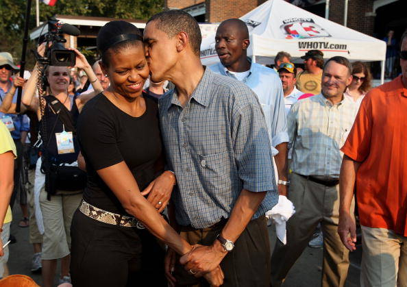 DES MOINES, IA - AUGUST 16:  Democratic Presidential Candidate Senator Barack Obama (D-IL) gives his wife Michelle a playful kiss as they tour the Iowa State Fair August 16, 2007 in Des Moines, Iowa. The fair runs until August 19th and is expected to draw about 1 million people. John Edwards also made a campaign stop at the fair today.  (Photo by Scott Olson/Getty Images)