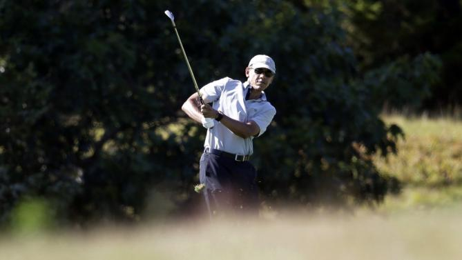 President Barack Obama watches the flight of his ball while golfing Wednesday, Aug. 12, 2015, at Farm Neck Golf Club, in Oak Bluffs, Mass., on the island of Martha's Vineyard. The president, first lady Michelle Obama, and daughter Sasha are vacationing on the island. (AP Photo/Steven Senne)