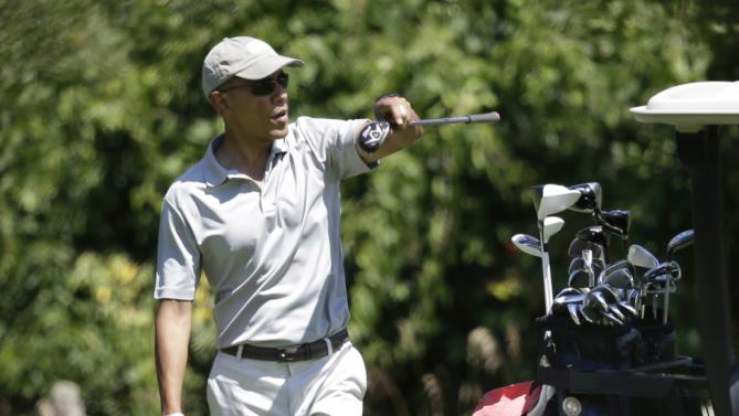 President Barack Obama looks in the direction of the fairway as he retrieves a club from a cart while golfing Saturday, Aug. 8, 2015, at Farm Neck Golf Club, in Oak Bluffs, Mass., on the island of Martha's Vineyard. Obama is spending his first full day of vacation on the island playing golf. (AP Photo/Steven Senne)