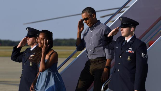 President Barack Obama salutes as he walks off of Air Force One with his daughter Malia at Andrews Air Force Base in Md., Sunday, Aug. 23, 2015. The president is returning to Washington after he and his family spent more than two weeks vacationing on the Massachusetts island of Martha's Vineyard. (AP Photo/Susan Walsh)