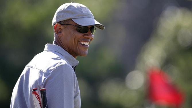 President Barack Obama smiles while golfing Wednesday, Aug. 12, 2015, at Farm Neck Golf Club in Oak Bluffs, Mass., on the island of Martha's Vineyard. The president, first lady Michelle Obama, and daughter Sasha are vacationing on the island. (AP Photo/Steven Senne)