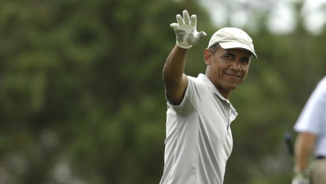 President Barack Obama waves while golfing Sunday, Aug. 23, 2015, at Farm Neck Golf Club, in Oak Bluffs, Mass., on the island of Martha's Vineyard. The president spent most of his two-week summer vacation on the golf course, at the beach, and dining out with his family. (AP Photo/Steven Senne)